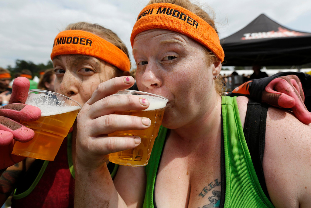 """. Heather Cozad (R) of the U.S. drinks beer with a friend after finishing the \""""Tough Mudder\"""" endurance event series in the Fursten Forest, a former British Army training ground near the north-western German city of Osnabrueck July 13, 2013. The hardcore but un-timed event over 16 km (10 miles) was designed by British Special Forces to test mental as well as physical strength. Some 4,000 competitors had to overcome obstacles of common human fears, such as fire, water, electricity and heights. REUTERS/Wolfgang Rattay"""