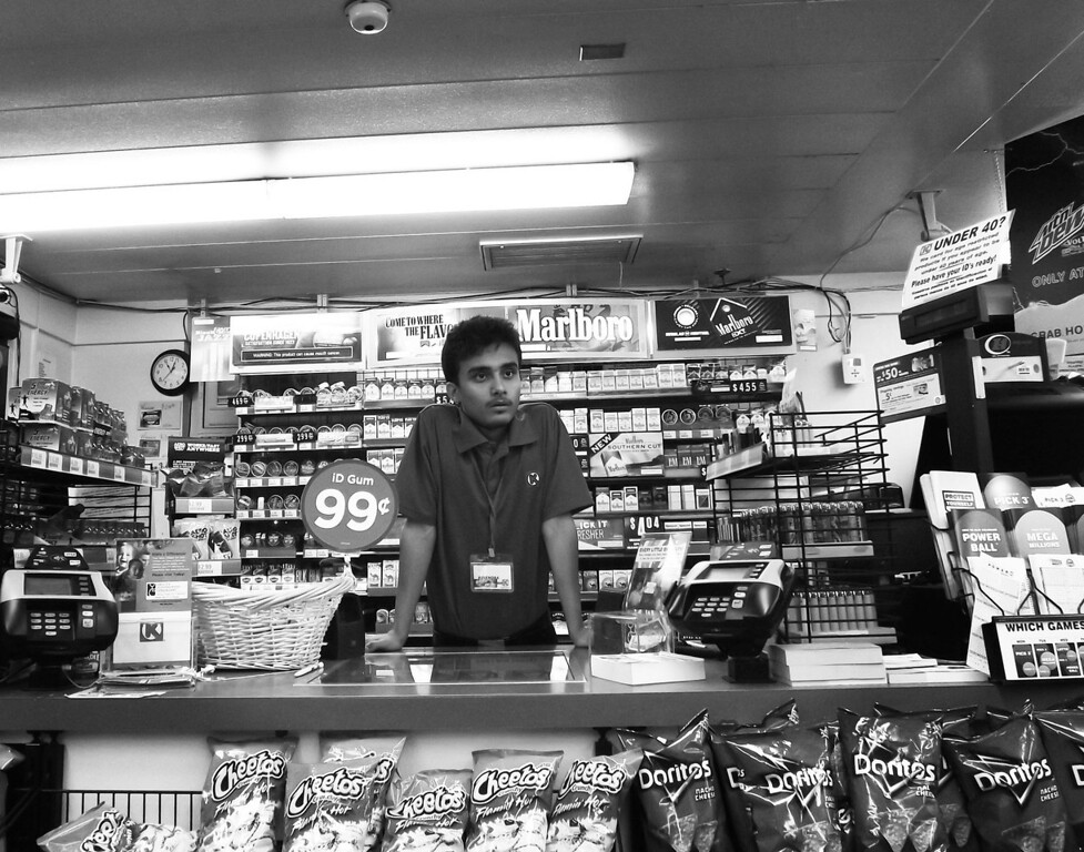 . I work at a gas station. This is me standing at the counter during a graveyard shift when there was nobody inside. This picture is black and white because nobody would want to work a graveyard shift at a gas station and I thought that making it black and white would tell the story. If this picture is colorful it would probably mean something else but since its black and white it�s a sad image. It�s me at 12am, alone, doing nothing, kind of scary, but nothing happened that day. I�m in college now and when I think about me working after ten years, you know, when I look at myself, I don�t see myself as something very specific but I have a dream inside me and everyday when I wake up I think about that dream. I feel like I need to go somewhere out of this country and there is someone who I can help there. I will be whatever I have to be to help that person, or those children or someone else. It could be the doctor in me, it could be a teacher in me, it could be a photographer in me, it could be a soccer player in me but I want to go help them. I don�t know maybe I will be shocked when I have to do something I don�t like but let it be. My ultimate goal is to get there and help them and be happy. I think I will have a smile when I go there and I get to help them. I remember when I was in the refugee camp I would see United Nations workers there who didn�t speak Nepali. Even in the refugee camp I thought I want to be like them. I want to help others. I always felt I was more privileged then others. I had a poster on my wall from the World Refugee Day somewhere in Africa. It was of long line of people on a bridge getting kicked out of their country, I always thought, I have school to go to in the refugee camp. I have clothes. I have a hut of bamboo. I had something over my head that was protecting me from the rain, so I always thought I was more privileged. I thought I was not asking for something because I was helpless. I thought there were other people who needed help even though I was in the refugee camp. (Photograph by Birendra Dikhal)