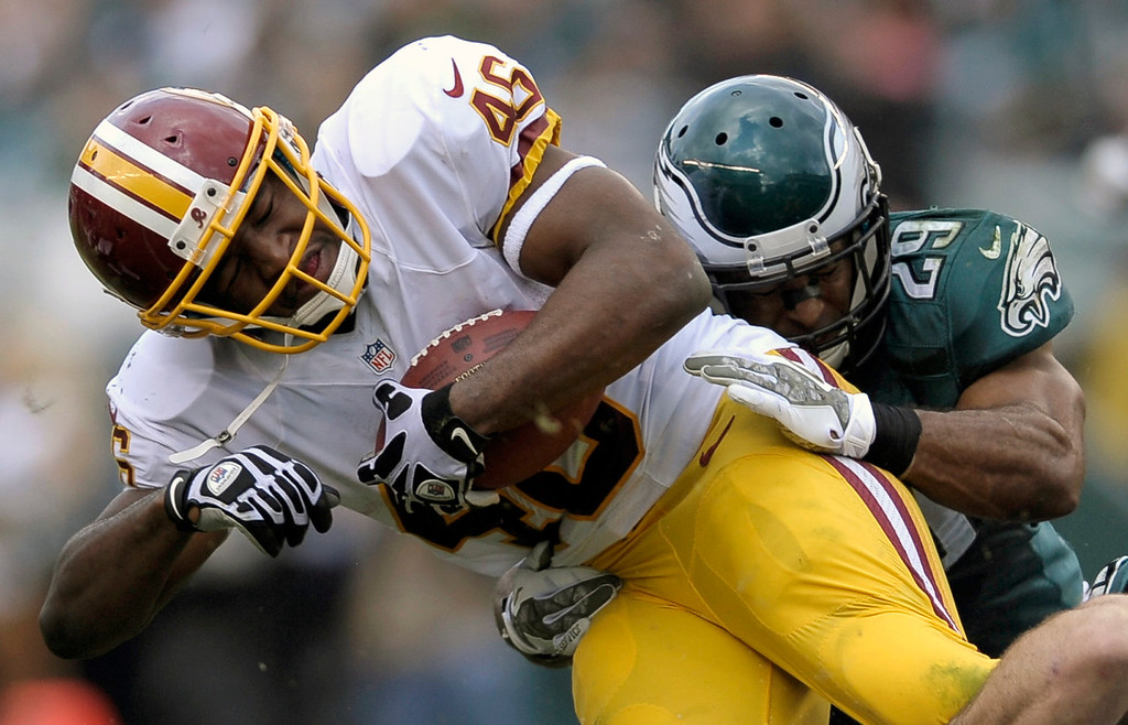 . Washington Redskins running back Alfred Morris, left, is stopped by Philadelphia Eagles strong safety Nate Allen during the first half of an NFL football game in Philadelphia, Sunday, Nov. 17, 2013. (AP Photo/Michael Perez)