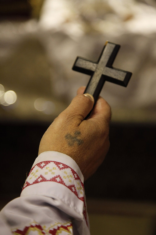 . A monk bearing a tattoo of a cross prays at the ancient monastery of St. Anthony, southeast of Cairo, Egypt on Tuesday, April 16, 2013. In a cave high in the desert mountains of eastern Egypt, the man said to be the father of monasticism took refuge from the temptations of the world some 17 centuries ago. The monks at the St. Anthony\'s Monastery bearing his name continue the ascetic tradition. But even they are not untouched by the turbulent times facing Egypt\'s Christians, defiantly vowing their community\'s voice won\'t be silenced amid Islamists\' rising power. (AP Photo/Manoocher Deghati)