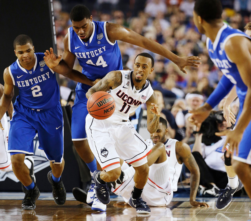 . Connecticut guard Ryan Boatright (11) gets past Kentucky guard Aaron Harrison (2), pk44n=, as guard Andrew Harrison (5) looks on during the first half of the NCAA Final Four tournament college basketball championship game Monday, April 7, 2014, in Arlington, Texas. (AP Photo/David J. Phillip)