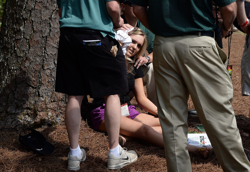 . A woman holds a towel after being hit by a ball played by Ben Crenshaw of the US on the eight fairway during the second round of the 78th Masters Golf Tournament at Augusta National Golf Club on April 11, 2014 in Augusta, Georgia. AFP PHOTO/Jim WATSON/AFP/Getty Images