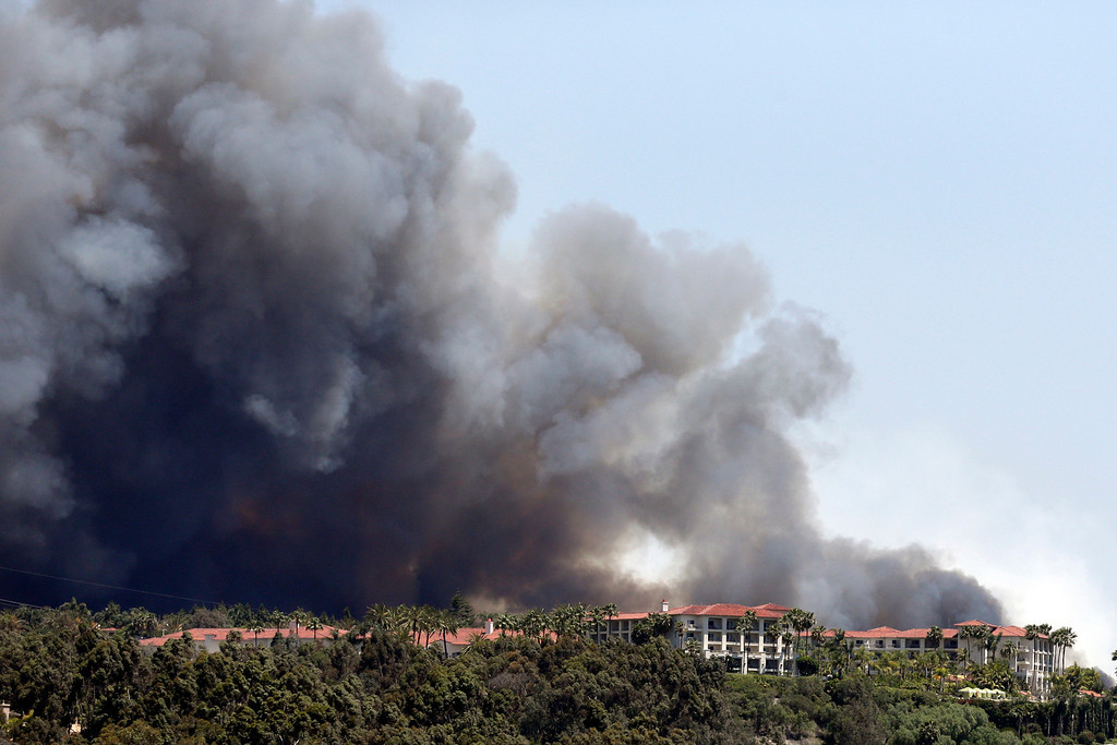 . Wildfire approaches buildings Wednesday, May 14, 2014, in Carlsbad, Calif. More wildfires broke out Wednesday in San Diego County threatening homes in Carlsbad and forcing the evacuations of military housing and an elementary school at Camp Pendleton as Southern California is in the grip of a heat wave. (AP Photo)