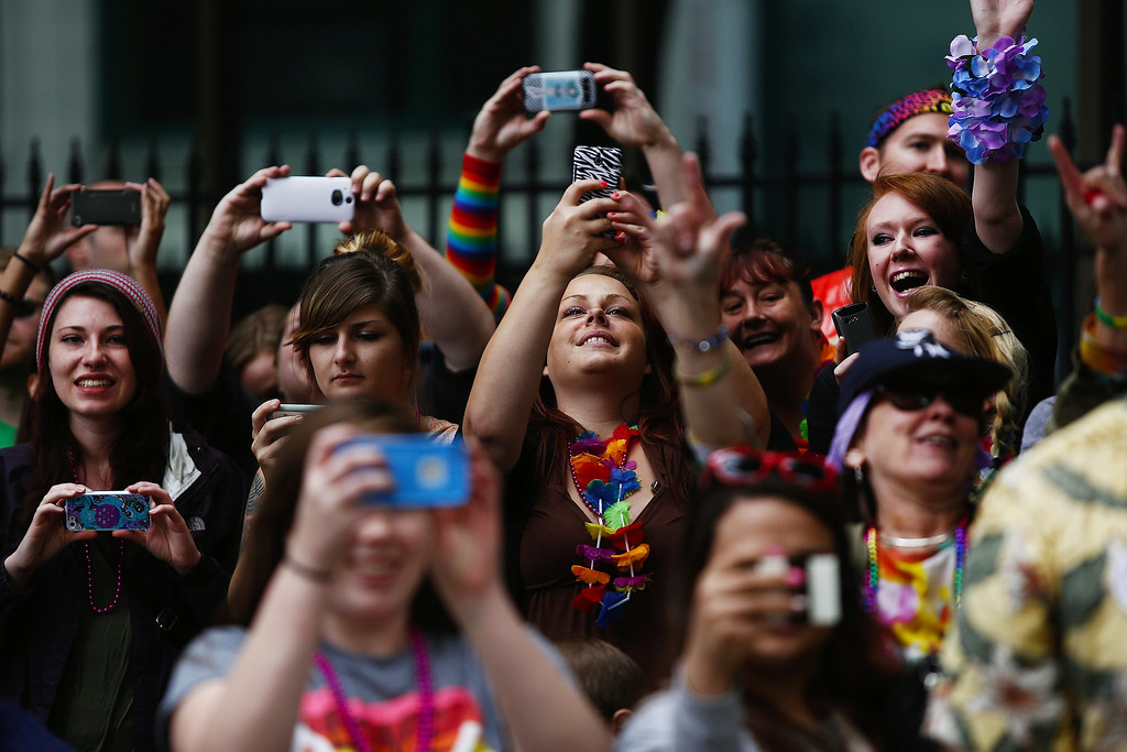 ". Fans take photos of Macklemore sitting atop a Cadillac as he passes by Westlake Park during the 40th annual Pride Parade on Sunday, June 29, 2014, in Seattle. This year\'s theme ó ""Generations of Pride\""ó honors civil rights battles in the city that elected its first openly gay mayor last November. (AP Photo/The Seattle Times, Lindsey Wasson)"