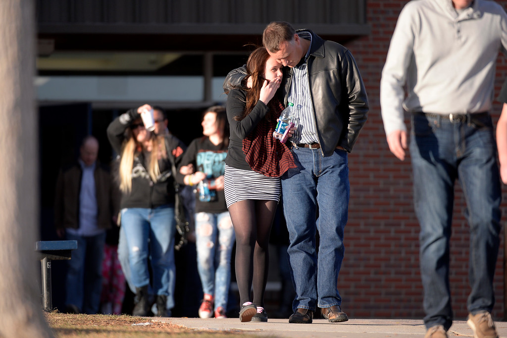 . CENTENNIAL, CO - Bianca Britz, Freshman at Arapahoe gets a hug from her dad Stephin Britz as they leave Euclid Middle School after getting bused their from Arapahoe High School December 13, 2013. A gunman at the school was targeting a teacher at the school. The gunman shot two students in the process and then turned the gun on himself. (Photo by John Leyba/The Denver Post)