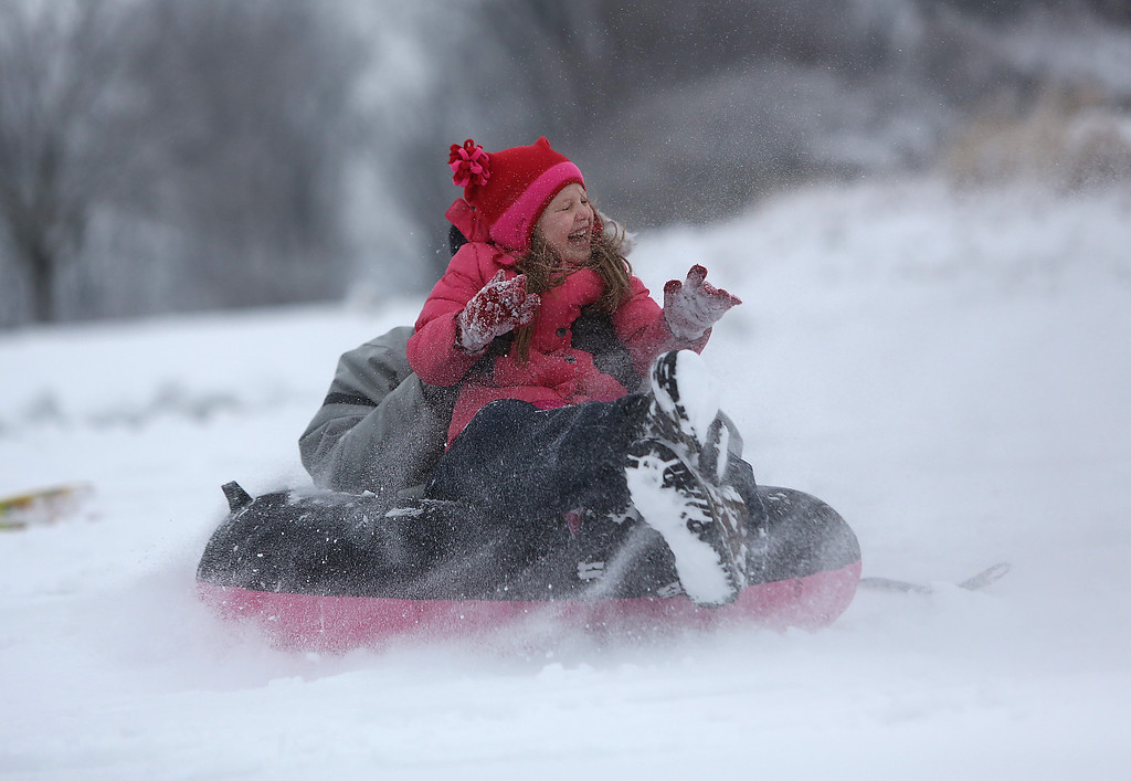 . Eva Heikenfeld, 5, from Mt. Lookout, laughs as she goes down the hill on a sled with her father Shane Heikenfeld at Ault Park in Cincinnati on Wednesday, March 6, 2013.   The National Weather Service has lifted winter storm warnings across Ohio, after a late-season storm dumped a half foot of snow or more on much of the state. Some areas in western Ohio got as much as 9 inches of snow before the storm moved on through the state eastward. (AP Photo/The Cincinnati Enquirer, Leigh Taylor)