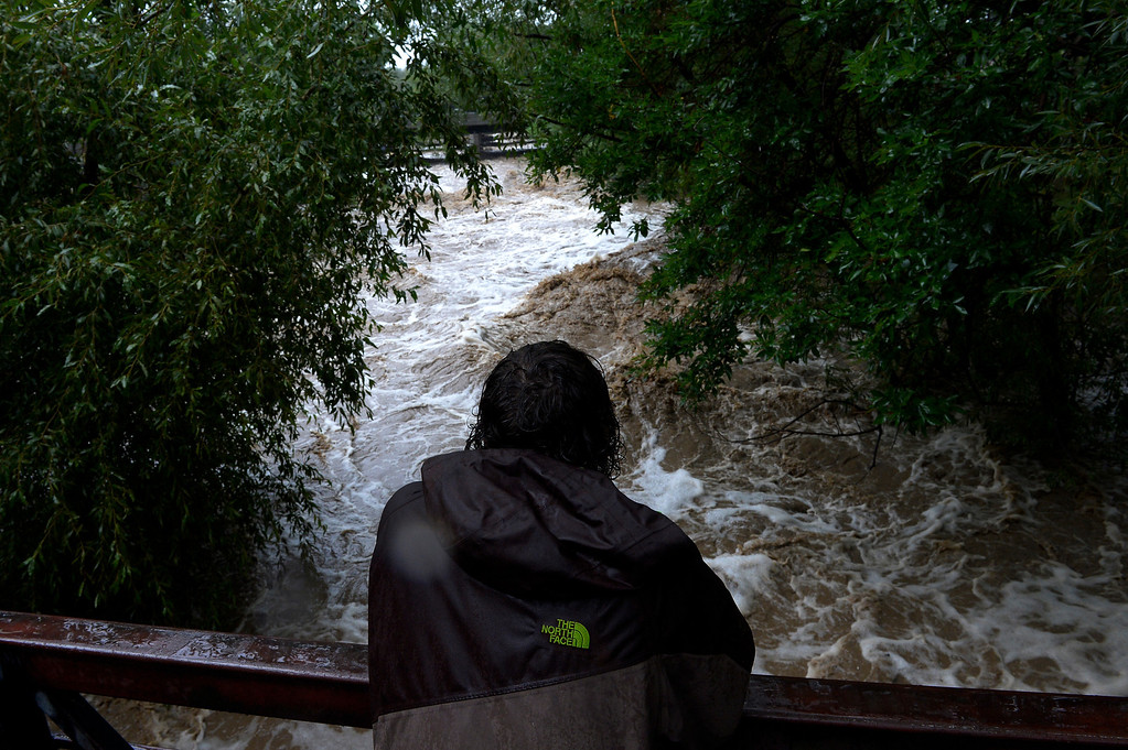 . BOULDER, CO. - SEPTEMBER12:  Marcus Rinedollar watches the raging Boulder Creek from a pedestrian bridge in Boulder, CO September 12, 2013. Record-breaking rain turned normally quiet creeks into raging, brown torrents that swept through Boulder on Thursday, flooding homes, swamping cars and closing roads and schools. (Photo By Craig F. Walker / The Denver Post)