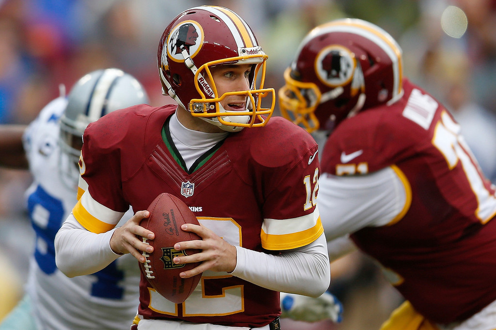 . Washington Redskins quarterback Kirk Cousins looks for an opening to pass during the first half of an NFL football game against the Dallas Cowboys in Landover, Md., Sunday, Dec. 22, 2013. (AP Photo/Evan Vucci)