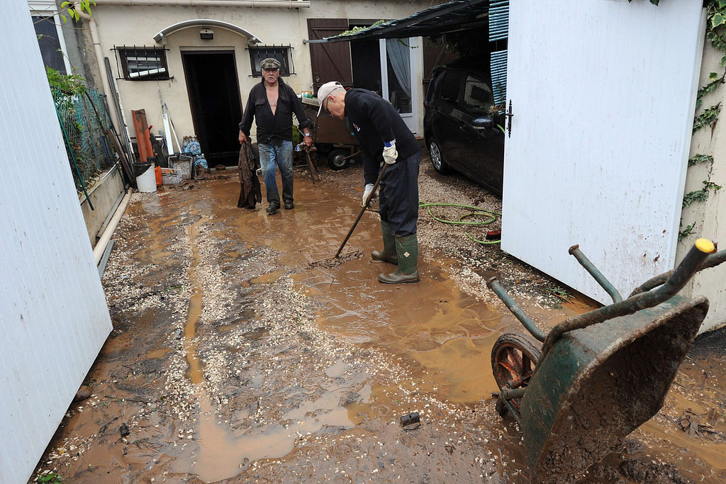 """. TOPSHOTS Pepole clean a house on Januray 20, 2014 in La Londe-les-Maures, southeastern France. River levels were receding early today in southeastern France after \""""historic\"""" floods left two people dead and more than 150 were airlifted to safety. A third man disappeared while out on his boat and 4,000 homes have been left without power after the deluge in the department of Var, they said. Local official Laurent Cayrel said one of the victims, a 73-year-old man, died in his basement, while the other was swept away in his car.  AFP PHOTO / BORIS HORVATBORIS HORVAT/AFP/Getty Images"""