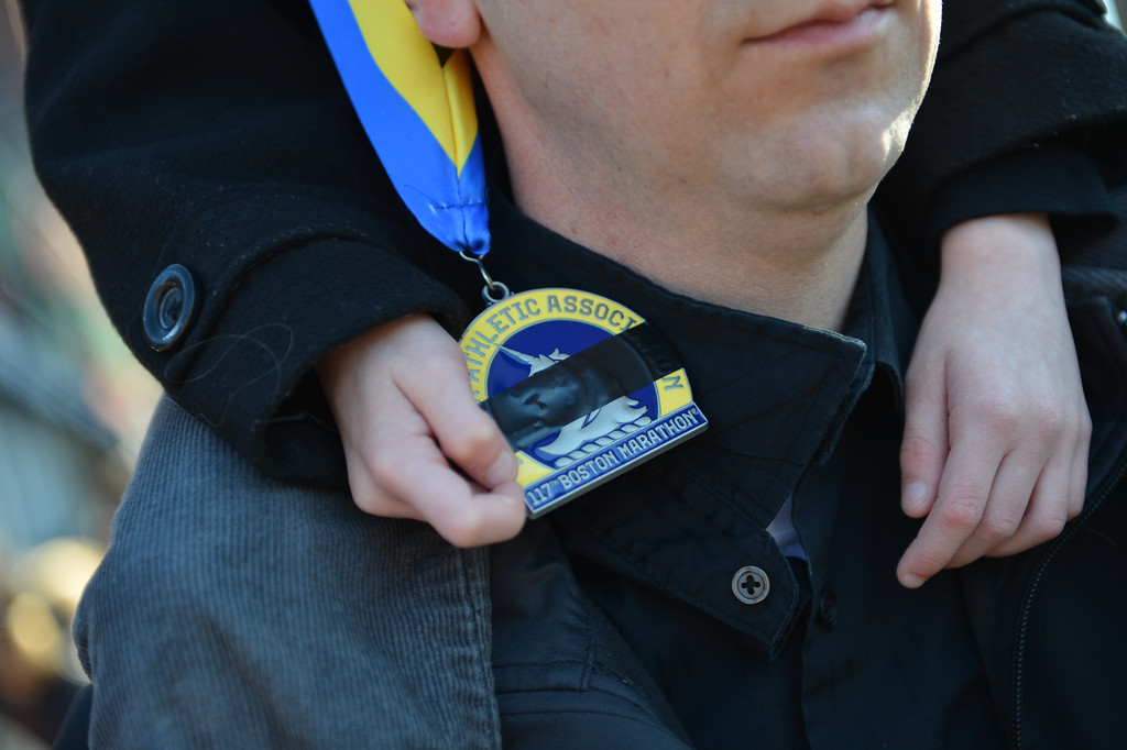 . A young boy holds a Boston Marathon Medal with black tape, signifying mourning, as he and his father stand near the Cathedral of the Holy Cross as US President Barrack Obama and wife Michelle attend an interfaith prayer service to honor the victims of the Boston Marathon bombings April 18, 2013 in the South End neighborhood of Boston, Massachusetts.  AFP PHOTO/Stan  HONDA/AFP/Getty Images