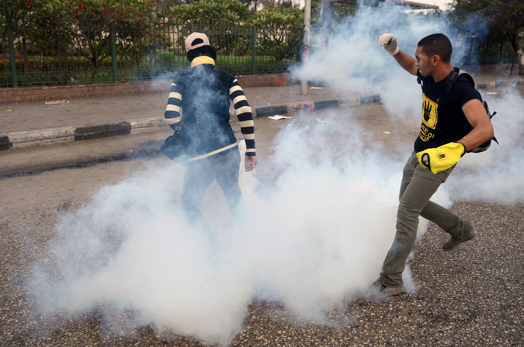 . Muslim Brotherhood and ousted President Mohamed Morsi supporters kick back tear gas canister during clashes with Egyptian security forces in Cairo on November 29, 2013.   AFP PHOTO/MOHAMED EL-SHAHED/AFP/Getty Images