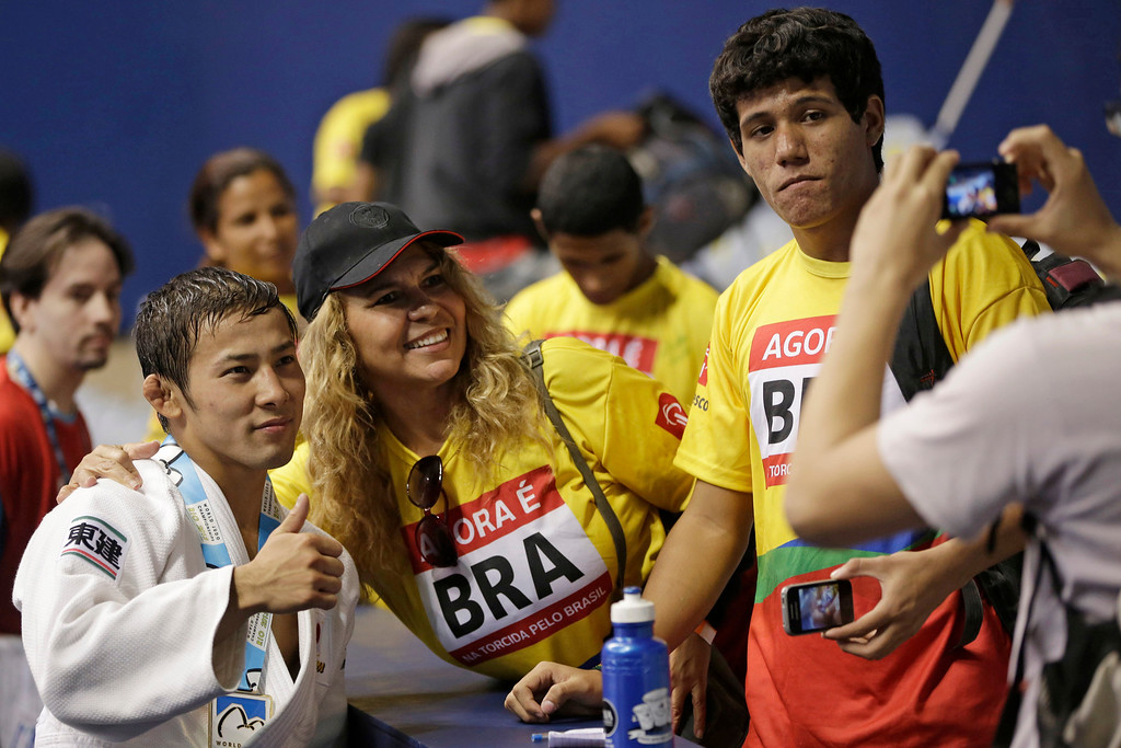 . Naohisa Takato, from Japan, left, poses for photos with fans after winning the men\'s -60kg final match at the World Judo Championships in Rio de Janeiro, Brazil, Monday, Aug. 26, 2013.  Takato defeated Amartuvshin Dashdavaa, from Mongolia to win the gold medal. (AP Photo/Felipe Dana)