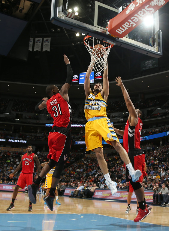 . Denver Nuggets guard Evan Fournier, center, of France, goes up for basket between Toronto Raptors guard Terrence Ross, left, and forward Chuck Hayes in the fourth quarter of an NBA basketball game in Denver on Friday, Jan. 31, 2014. (AP Photo/David Zalubowski)