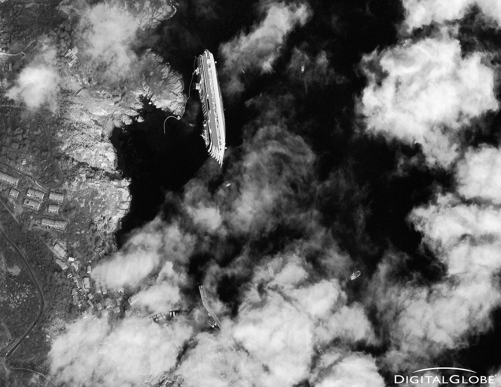 . The luxury cruise ship Costa Concordia is shown run aground off the coast of Giglio in this January 17, 2012 DigitalGlobe handout satellite photo obtained by Reuters January 18, 2012. Eleven people are confirmed dead and at least 23 are still missing from more than 4,200 passengers and crew after the Concordia ran aground two hours into a week-long cruise of the western Mediterranean      REUTERS/DigitalGlobe/Handout