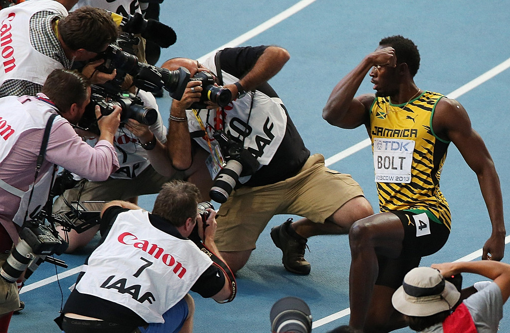 . Photographers take pictures of Jamaica\'s Usain Bolt (R) as he celebrates after winning the men\'s 200 metres final at the 2013 IAAF World Championships at the Luzhniki stadium in Moscow on August 17, 2013. LOIC VENANCE/AFP/Getty Images