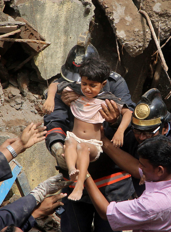 . Indian Fire officials rescue a girl from the debris of a collapsed building in Mumbai, India, Friday, Sept. 27, 2013.  (AP Photo)