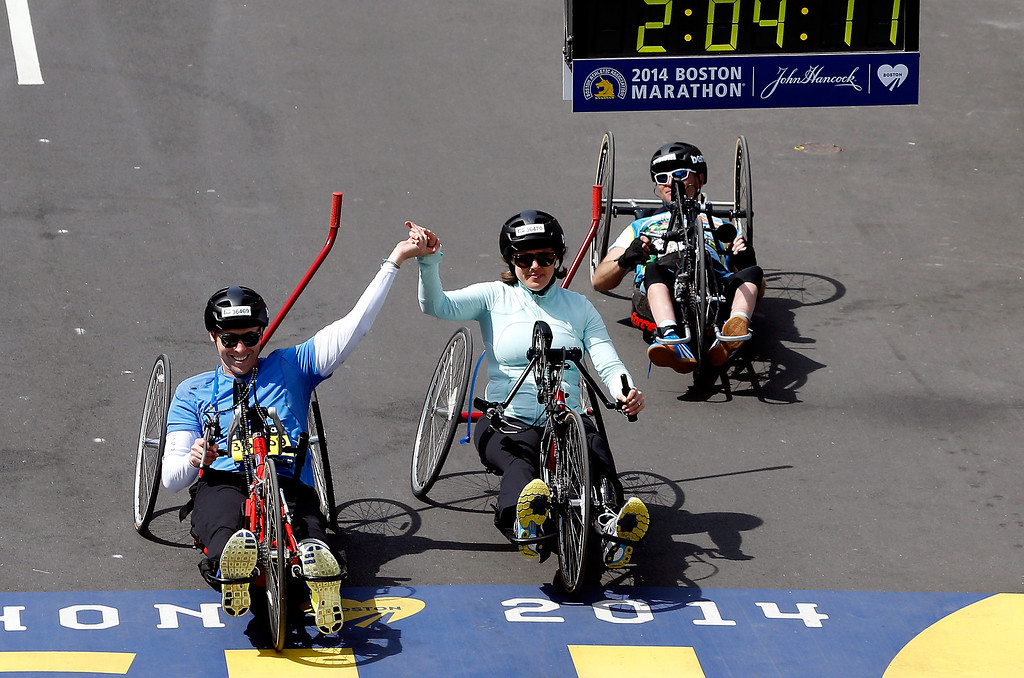 . Handcycle division competitors cross the finish line of the 118th Boston Marathon on April 21, 2014 in Boston, Massachusetts.  (Photo by Jim Rogash/Getty Images)