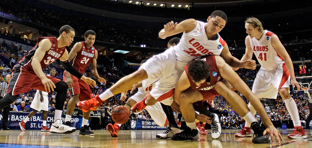 . New Mexico\'s Merv Lindsay (22) and Stanford\'s Stefan Nastic, bottom, chase a loose ball during the second half of a second-round game in the NCAA college basketball tournament, Friday, March 21, 2014, in St. Louis. Stanford won the game 58-53. (AP Photo/Charlie Riedel)