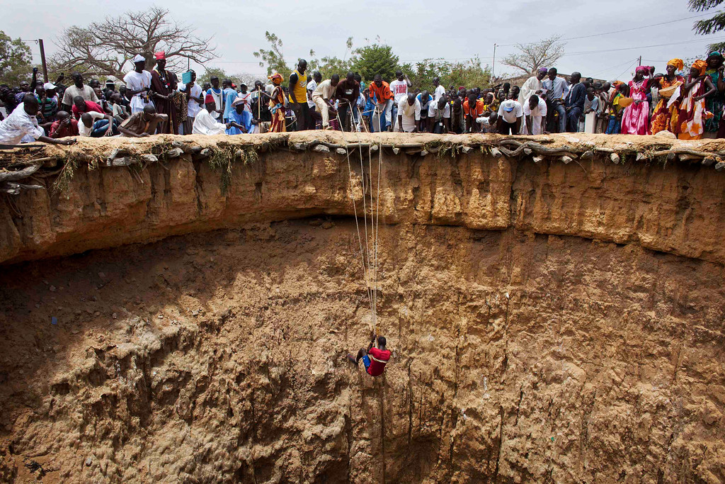 . People watch a man descend into a large former well during a traditional ceremony in the village of Ndande, May 19, 2013. Every year, inhabitants of the village take part in a Sufi Muslim ceremony called Gamou-Ndande. The ceremony combines nights of praying and chanting as well as traditionally animist ceremonies. The well, called Kalom, was the site of historic battles in Senegalese history. According to local historian Baye Niass, the well dates back to the 16th century. Today there is no water in the former well and it is used for ceremonial purposes. Niass says the well measure 36 meters in depth an 11m in diameter. Picture taken May 19, 2013.  REUTERS/Joe Penney