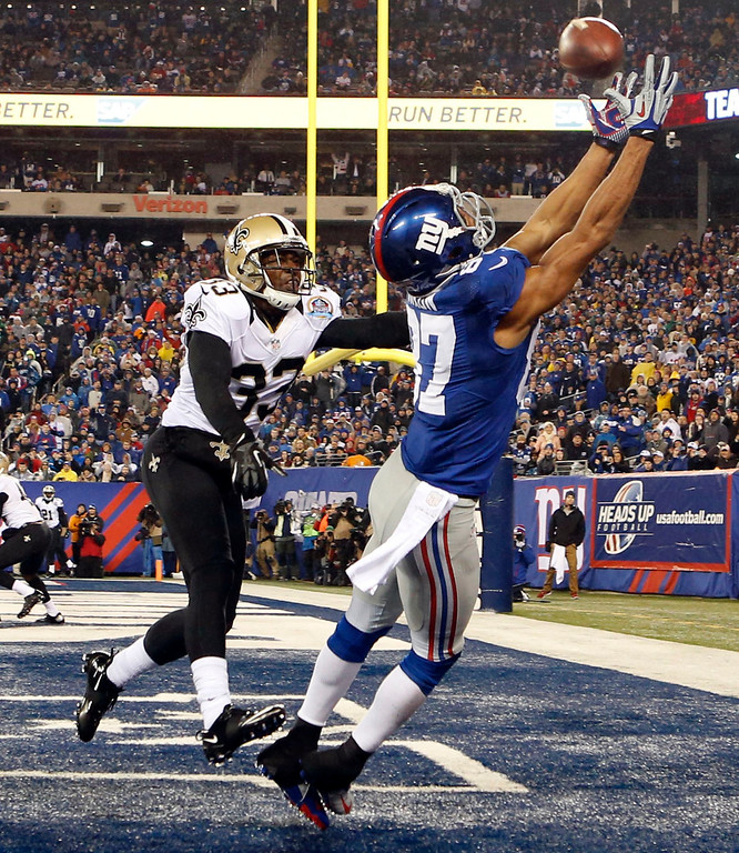 . New York Giants wide receiver Domenik Hixon catches a touchdown pass in front of New Orleans Saints defender Jabari Greer during the second quarter of their NFL football game in East Rutherford, New Jersey, December 9, 2012. REUTERS/Mike Segar