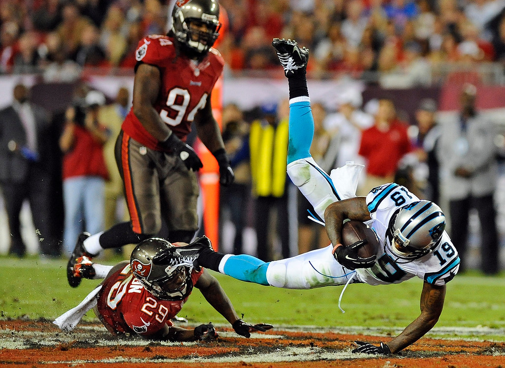 . Carolina Panthers wide receiver Ted Ginn (19) is tripped by Tampa Bay Buccaneers cornerback Leonard Johnson (29) after a reception during the second quarter of an NFL football game on Thursday, Oct. 24, 2013, in Tampa, Fla. Buccaneers\' Adrian Clayborn (94) chases on the play. (AP Photo/Brian Blanco)