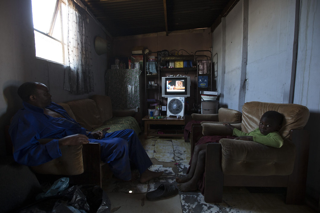 . A father and son watch the funeral of former South African President Nelson Mandela on television in their home in Soweto Township on December 15, 2013 in Soweto, South Africa. Mr. Mandela passed away on the evening of December 5, 2013 at his home in Houghton at the age of 95. Mandela became South Africa\'s first black president in 1994 after spending 27 years in jail for his activism against apartheid in a racially-divided South Africa.  (Photo by Oli Scarff/Getty Images)