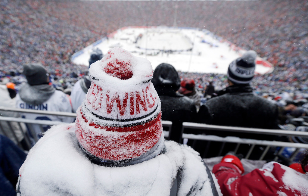 . A Detroit Red Wings fan coated with snow watches during the third period of the Winter Classic outdoor NHL hockey game against the Toronto Maple Leafs at Michigan Stadium in Ann Arbor, Mich., Wednesday, Jan. 1, 2014. (AP Photo/Carlos Osorio)