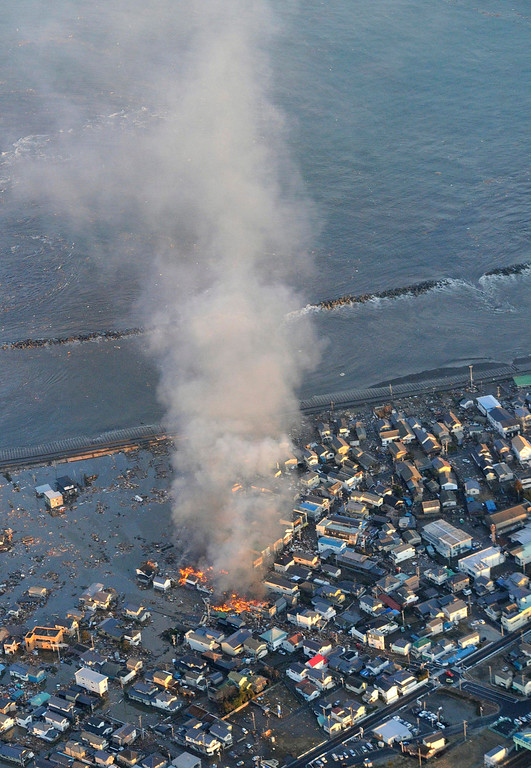 . Fire smokes billow from residences as a coastal area is flooded by waters after a tsunami in Iwaki, Fukushima prefecture (state), Japan, Friday, March 11, 2011. The powerful tsunami spawned by the largest earthquake in Japan\'s recorded history slammed the eastern coast Friday, sweeping away boats, cars, homes and people as widespread fires burned out of control. (AP Photo/Kyodo News)
