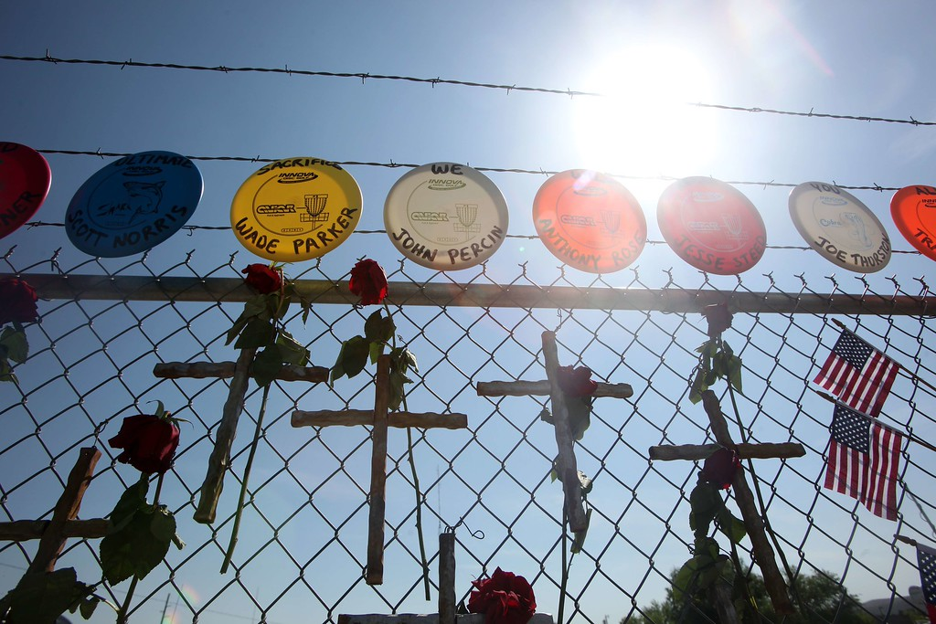 . Crosses, roses and frisbees with the names of the 19 fallen firefighters are mounted on a fence outside of Granite Mountain Hotshots Fire Station 7 in Prescott, Arizona July 2, 2013.  AFP PHOTO / KRISTA  Kennell/AFP/Getty Images