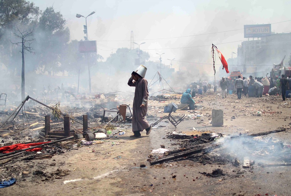 . A supporter of Egypt\'s ousted president Mohamed Morsi walks through the debris following clashes with police in Cairo on August 14, 2013, as security forces backed by bulldozers moved in on two huge pro-Morsi protest camps, launching a long-threatened crackdown that left dozens dead.  AFP PHOTO / MOSAAB  EL-SHAMY/AFP/Getty Images