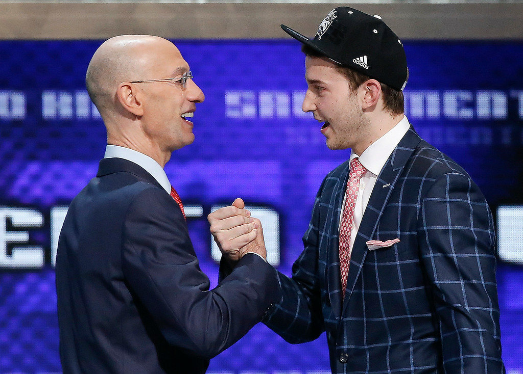 . Nik Stauskas, right, is greeted by NBA Commissioner Adam Silver after being selected eighth overall by the Sacramento Kings during the 2014 NBA draft, Thursday, June 26, 2014, in New York.  (AP Photo/Kathy Willens)
