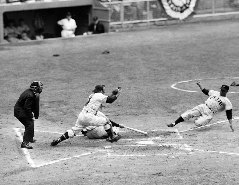 . Monte Irvin, New York Giants\' left fielder, slides home in the first inning of the World Series opener at Yankee Stadium, New York, Oct. 4, 1951, as he makes the first home plate steal in a World Series game in 30 years.  Yankees catcher Yogi Berra steps up to the plate with the ball in vain while batter Bobby Thomson falls away from the plate.  (AP Photo)