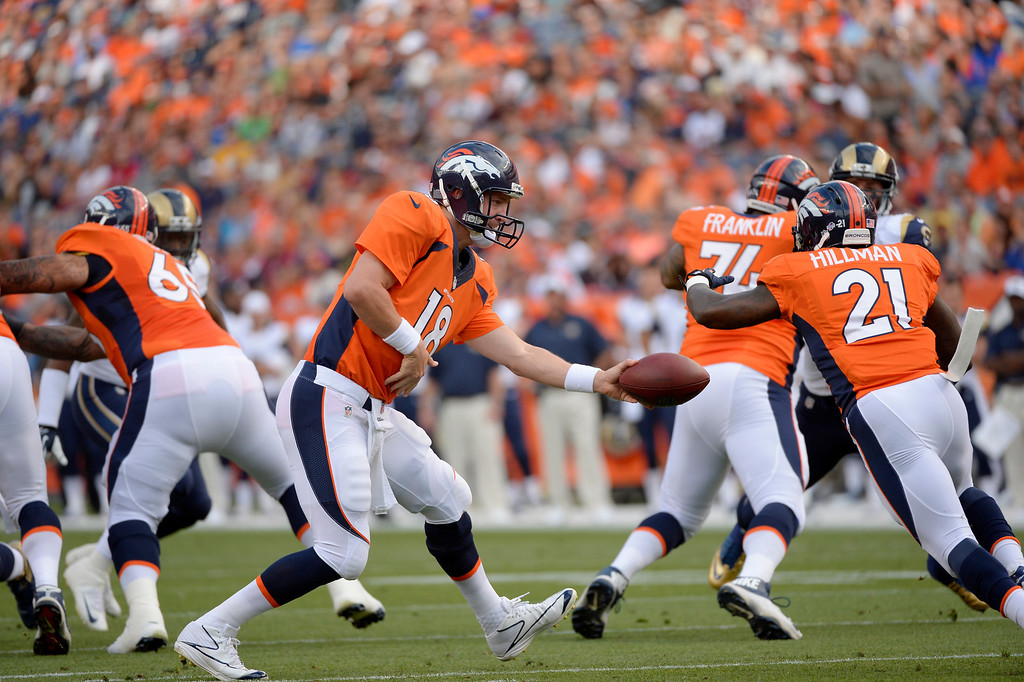 . DENVER, CO. - August 24: quarterback Peyton Manning (18) of the Denver Broncos hands off to running back Ronnie Hillman (21) of the Denver Broncos during the first half of action. The Denver Broncos vs the St. Louis Rams during the 3rd pre-season game of the season at Sports Authority Field at Mile High. August 24, 2013 Denver, Colorado. (Photo By Joe Amon/The Denver Post)