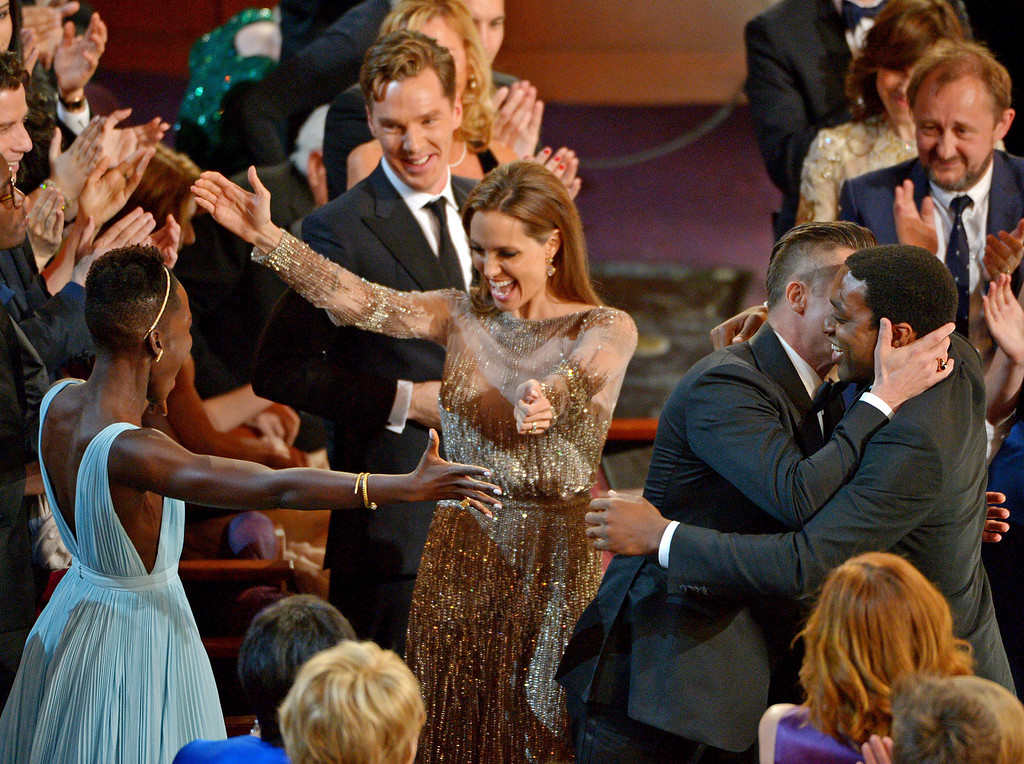 ". Lupita Nyong\'o, left, prepares to embrace Angelina Jolie, as Benedict Cumberbatch, background center, looks on, and Brad Pitt, embraces Chiwetel Ejiofor, right, after ""12 Years a Slave\"" was announced the winner for best picture during the Oscars at the Dolby Theatre on Sunday, March 2, 2014, in Los Angeles.  (Photo by John Shearer/Invision/AP)"