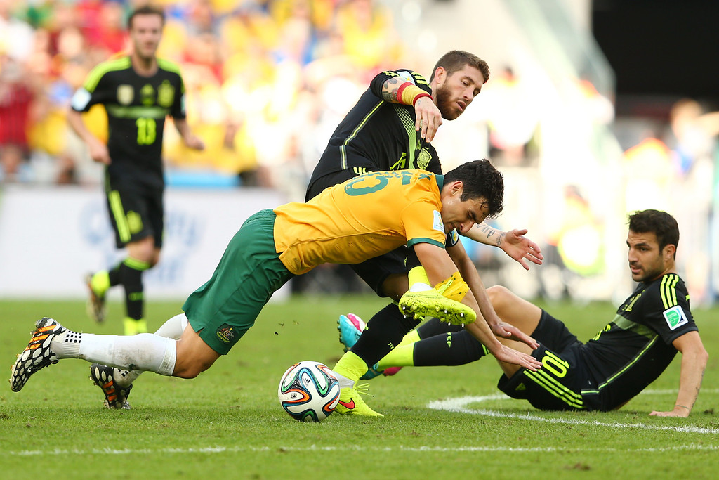 . Mile Jedinak of Australia and Sergio Ramos of Spain compete for the ball during the 2014 FIFA World Cup Brazil Group B match between Australia and Spain at Arena da Baixada on June 23, 2014 in Curitiba, Brazil.  (Photo by Quinn Rooney/Getty Images)
