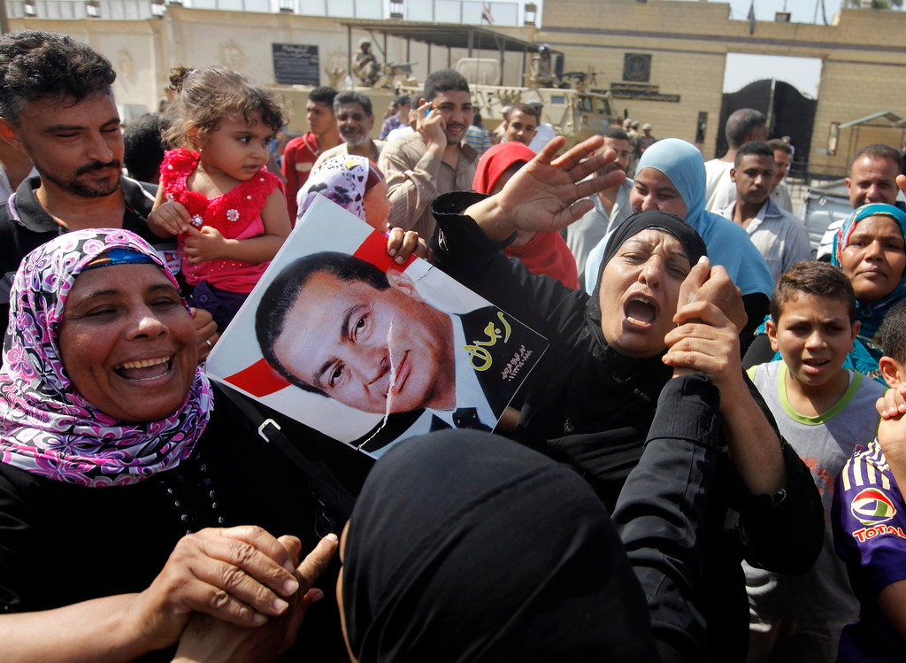""". Supporters of Egypt\'s deposed autocrat Hosni Mubarak hold a poster of him and chant slogans in front of Torah Prison where he has been held, in Cairo, Egypt, Thursday, Aug. 22, 2013. The Arabic writing on the poster reads \""""men of Mubarak.\"""" Egypt\'s ousted leader Hosni Mubarak, wearing a white shirt and loafers while flashing a smile, was released from prison Thursday and transported to a military hospital in a Cairo suburb where he will be held under house arrest. (AP Photo/Amr Nabil)"""