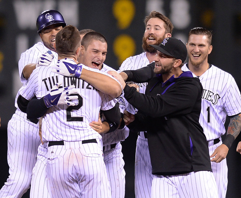 . Nolan Arenado, center, grabbed Troy Tulowitzski as teammates gathered around them after he doubled to drive in two runs in the bottom of the ninth inning to win the game.   (Photo by Karl Gehring/The Denver Post)