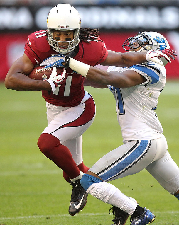 . Arizona Cardinals wide receiver Larry Fitzgerald (11) breaks the tackle of Detroit Lions cornerback Jacob Lacey during the first half of an NFL football game on Sunday, Dec. 16, 2012, in Glendale, Ariz. (AP Photo/Paul Connors)