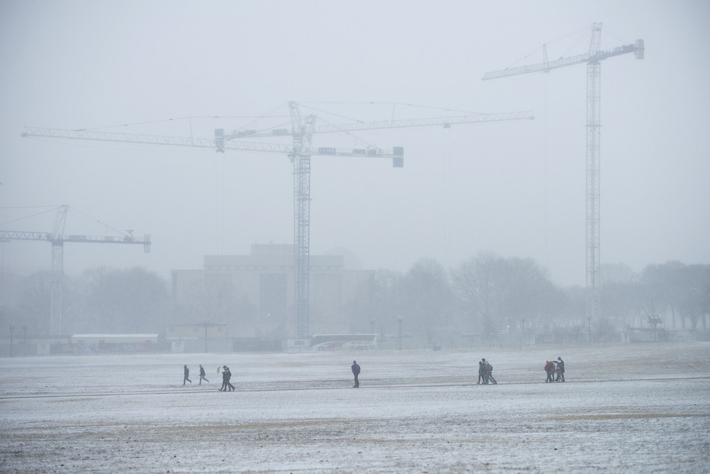 . People walk near construction cranes on the National Mall January 21, 2014 in Washington, DC. AFP PHOTO/Brendan SMIALOWSKI/AFP/Getty Images