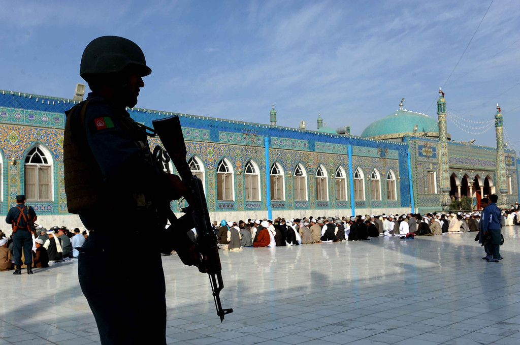 . Afghan policeman keep watch as worshippers offer Eid-al-Adha prayers in the main mosque in the city of Mazar-i-Sharif in Balkh province on October 15, 2013.  AFP PHOTO/ Farshad USYAN/AFP/Getty Images