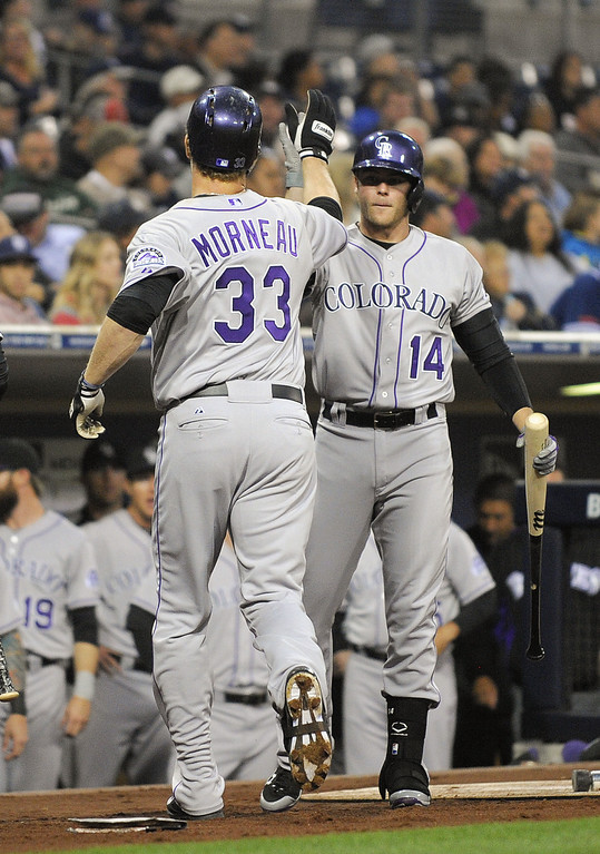 . SAN DIEGO, CA - APRIL 16:  Justin Morneau #33 of the Colorado Rockies is congratulated by Josh Rutledge #14  after hitting a solo home run during the second inning of a  baseball game against the San Diego Padres at Petco Park April 16, 2014 in San Diego, California.  (Photo by Denis Poroy/Getty Images)