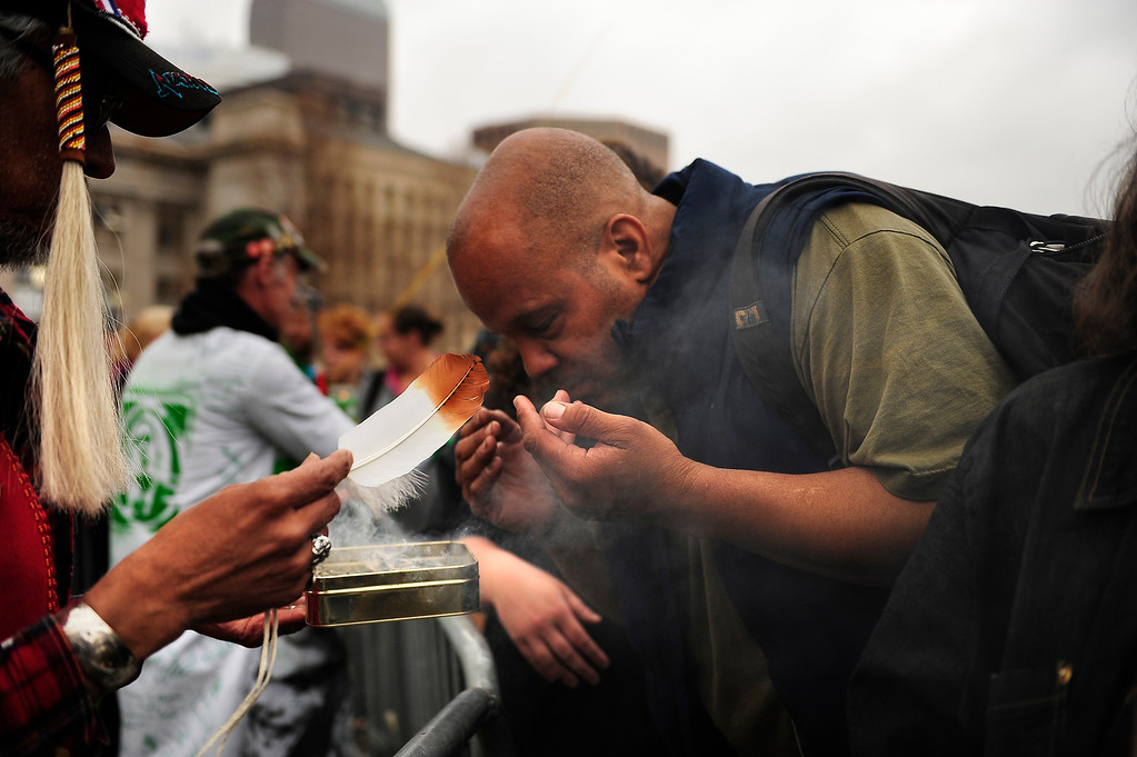 . Keith Johnson Jr. of Lakewood uses incense to cleanse the sprit of visitors to the Annual Denver 420 Rally in Civic Center Park.      Joe Amon, The Denver Post