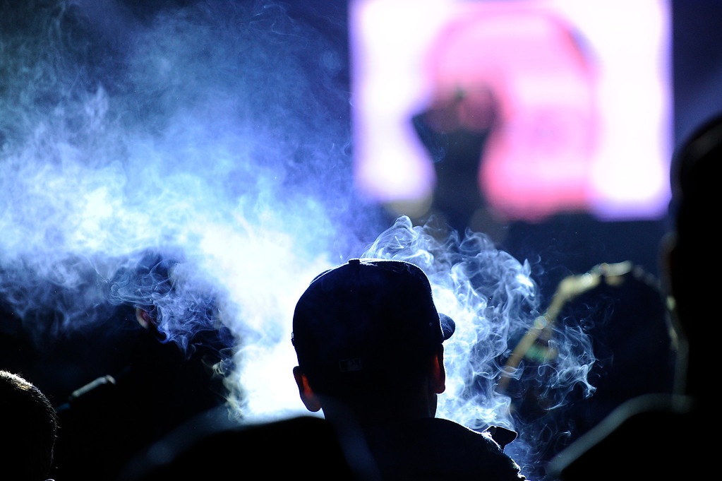 . DENVER, CO - APRIL 4: A cloud of smoke rises around a fan as he watches Earl Sweatshirt perform during the Snowball Music Festival at Sports Authority Field at Mile High Stadium on April 4, 2014 in Denver, Colorado. The Snowball Music Festival is celebrating its first year in Denver after spending the previous three years as a mountain based festival. (Photo by Seth McConnell/The Denver Post)