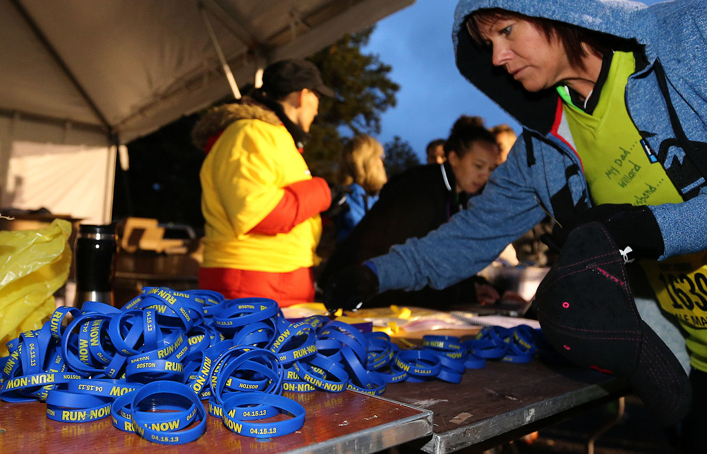 . SALT LAKE CITY, UT - APRIL 20: A runner grabs a bracelet to honor the victims of the Boston Marathon bombing before the start of the Salt Lake City Marathon on April 20, 2013 in Salt Lake City, Utah. Due to the bombings at the Boston Marathon on April 15, security was dramatically increased by law enforcement and Utah National Guard at the Salt Lake City Marathon. Organizers are asking spectators to leave backpacks at home. (Photo by George Frey/Getty Images)