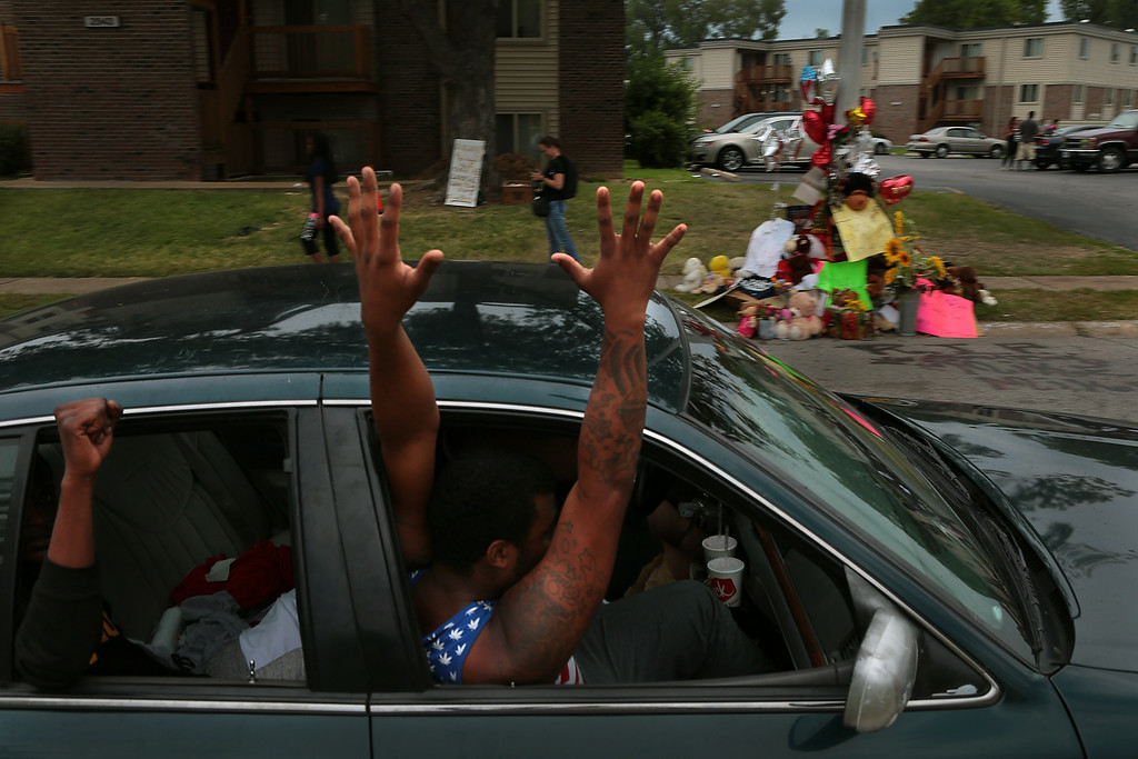 . Passengers in a car raise their hands as they pass the memorial where Michael Brown was shot dead in the Canfield Green Apartments on Friday, Aug. 15, 2014.   (AP Photo/St. Louis Post-Dispatch, Robert Cohen)