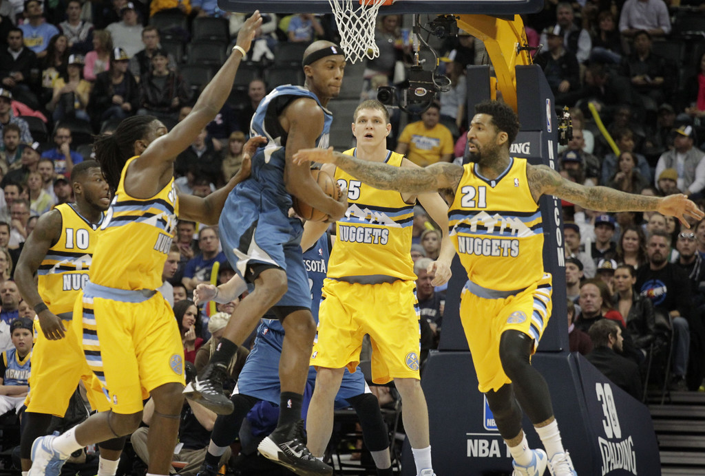 . Minnesota Timberwolves forward Corey Brewer, third from left, scoops up a loose ball against Denver Nuggets forwards Kenneth Faried (35) and Wilson Chandler (21) as Nuggets center Timofey Mozgov (25) backs up the play during the first quarter of an NBA basketball game in Denver, Friday, Nov. 15, 2013. (AP Photo/Joe Mahoney)