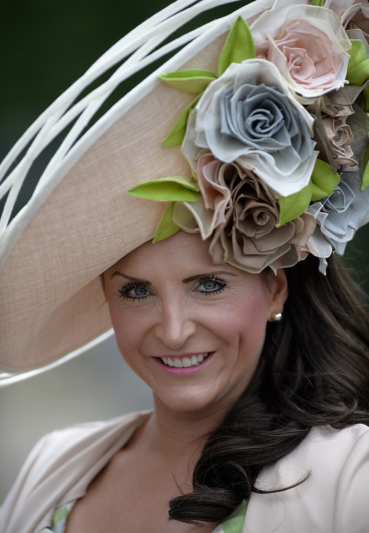 . A racegoers poses for a photograph during the first day of Royal Ascot, in Berkshire, west of London, on June 18, 2013. The five-day meeting is one of the highlights of the horse racing calendar.  Horse racing has been held at the famous Berkshire course since 1711 and tradition is a hallmark of the meeting. Top hats and tails remain compulsory in parts of the course while a daily procession of horse-drawn carriages brings the Queen to the course.  ADRIAN DENNIS/AFP/Getty Images