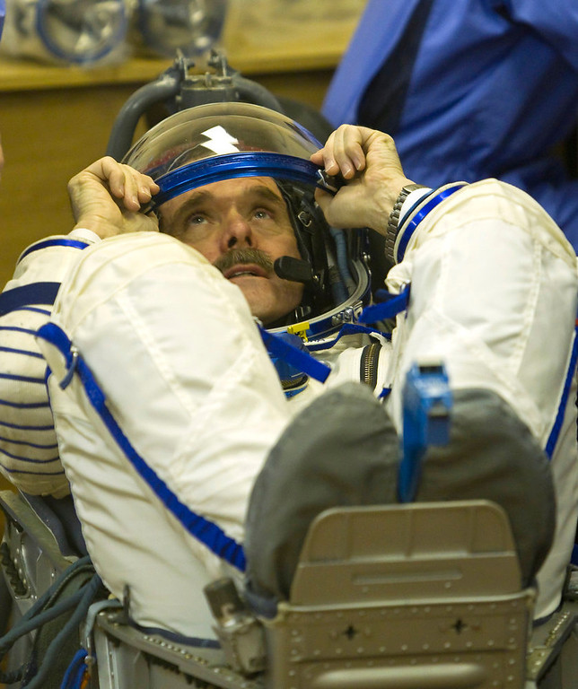 . The International Space Station (ISS) crew member Canadian astronaut Chris Hadfield looks on while specialists check his space suit at the Baikonur cosmodrome Kazakhstan Wednesday, Dec. 19, 2012.  (AP Photo/ Shamil Zhumatov, pool)