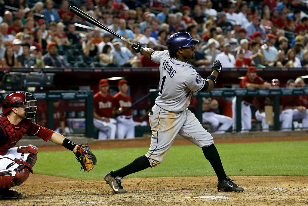 . Colorado Rockies\' Eric Young Jr. (1) connects on a double as Arizona Diamondbacks\' Miguel Montero looks on during the sixth inning of a baseball game, Sunday, April 28, 2013, in Phoenix. (AP Photo/Ross D. Franklin)