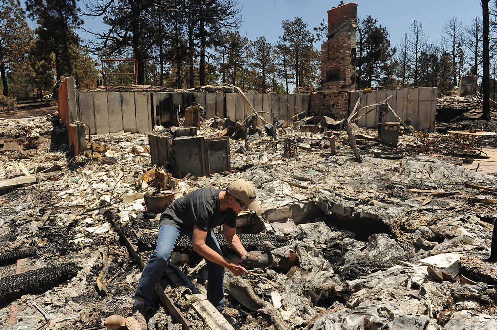 . BLACK FOREST, CO - JUNE 19:  Cindy Mitchell finds a ceramic duck, that had been on a shelf next to their hot tub,  from the ashes of her home on Darr Drive in Black Forest, CO on June 19, 2013.   Cindy and Ray Mitchell came home for the first time since the fire in Black Forest, CO on June 19, 2013.  Her husband Ray had seen the fire coming almost immediately as it had started just southwest of their home. Their\'s was one of the first houses to burn.  The couple had lived in the home for over 22 years and were even married on the property.  The Black Forest Fire stands at 85% containment and more and more homeowners are being allowed back into their homes for a few hours each day. 14, 280 acres have burned and the total number of homes lost increased to 509.  Photo by Helen H. Richardson/The Denver Post)